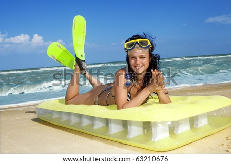 Smiling girl enjoying on an inflatable beach mattress - stock photo