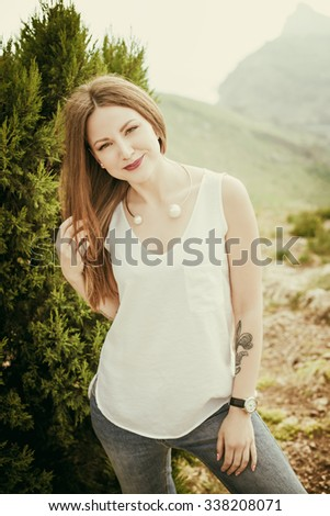 Smiling girl enjoys fine warm spring weather highly in mountains against the sea. Beautiful modern woman with long hair in a white shirt and blue jeans outdoors. slim tanned body,  thin nose