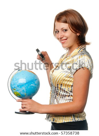 Smiling girl examines the globe through a magnifier