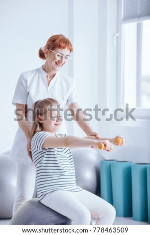 Smiling girl exercising with orange dumbbells with therapist's support