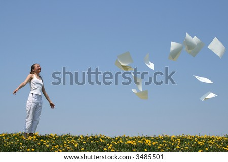 Smiling girl frees herself from paperwork and looks at blank paper sheets (with copy space) going away with the wind. - stock photo