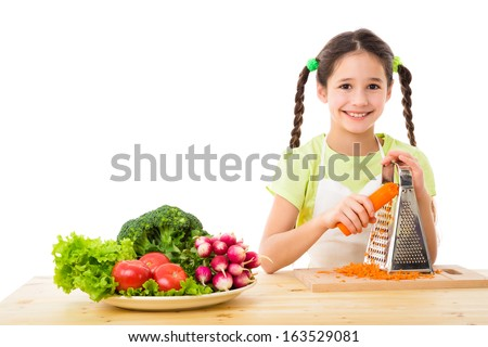 Smiling girl grate the carrots, cooking vegetables, isolated on white - stock photo