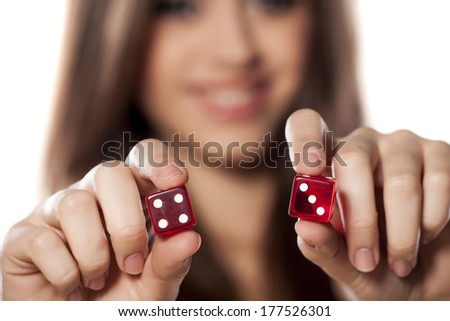 smiling girl holding a pair of dice for gambling with a combination of seven