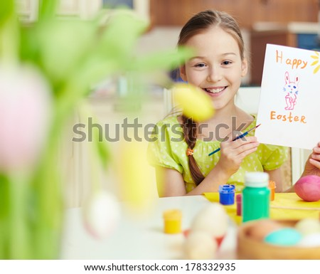 Smiling girl holding Easter greeting card - stock photo