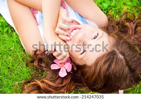 Smiling girl holding  flower lying on the grass - stock photo