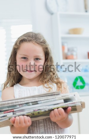 Smiling girl holding old newspapers for recycling - stock photo