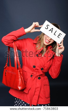 Smiling girl holding sale sign