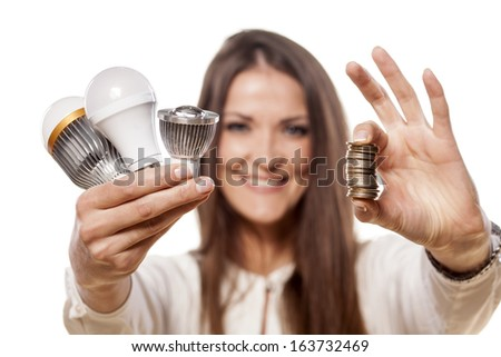 smiling girl holding the LED bulbs in one hand and a pile of coins in the other - stock photo