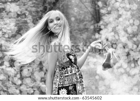 Smiling girl holds shoes in a hand. black a white portrait - stock photo