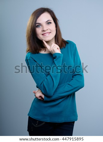smiling girl in a blue t-shirt with your finger touches the face on a gray background