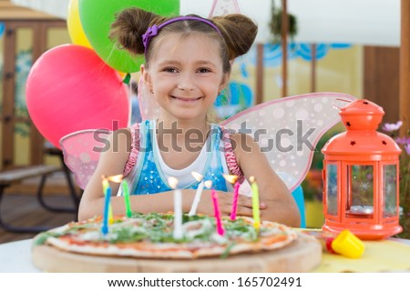 Smiling girl in a fairy costume with burning candles in pizza - stock photo