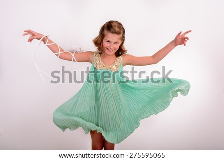 Smiling girl in a flowing turquoise dress on a white background