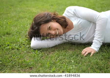 smiling girl in a grass field - stock photo