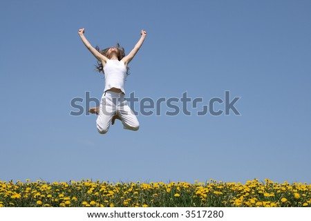 Smiling girl in a happy jump, looking up, in a flowering field. - stock photo