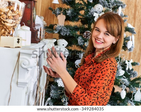 Smiling girl in a red dress holding a lantern and look at camera. Christmas interior