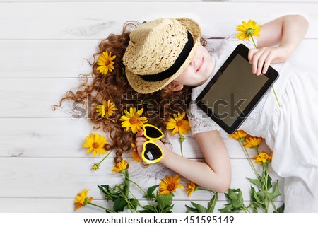Smiling girl in a straw hat resting on the tablet in her hands. Dreaming of a rustic holiday. - stock photo