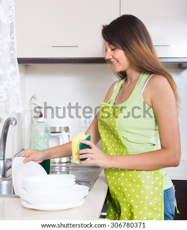 Smiling girl in apron washing plates with sponge in domestic kitchen