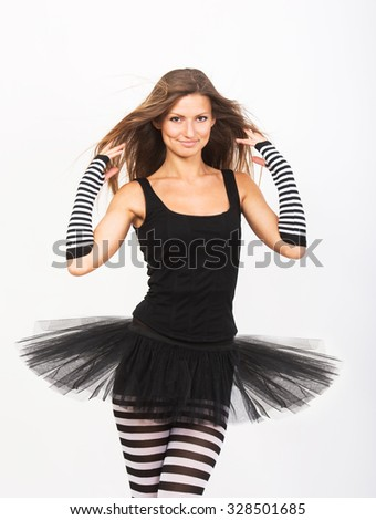 Smiling girl in black and white striped tights adjusting her hair