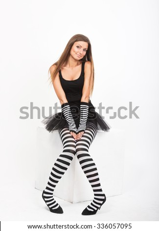 Smiling girl in black and white striped tights sitting on a white cube - stock photo