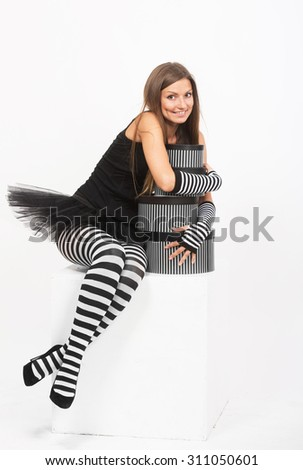 Smiling girl in black and white striped tights with the gift boxes - stock photo