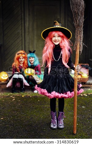 Smiling girl in costume of Halloween witch looking at camera with her friends on background - stock photo