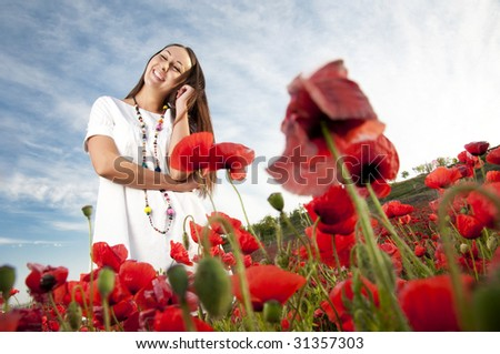 Smiling girl in field of poppy flowers - stock photo