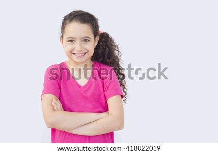 Smiling girl in fuchsia pink shirt crossing her hands - stock photo