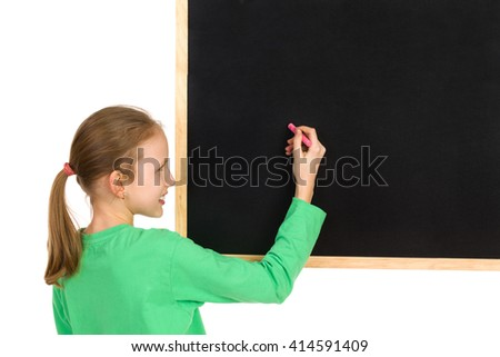Smiling girl in green blouse holding white chalk writing on a blackboard. Head and shoulders studio shot isolated on white.