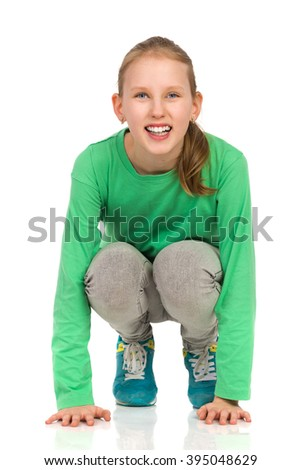 Smiling girl in green blouse, jeans and sneakers crouching on a floor. Full length studio shot isolated on white. - stock photo