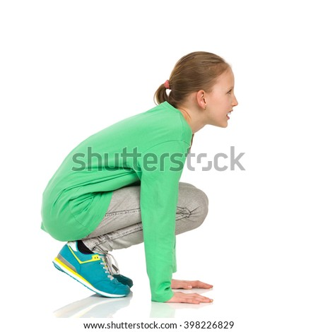 Smiling girl in green blouse, jeans and sneakers crouching on a floor. Side view. Full length studio shot isolated on white. - stock photo