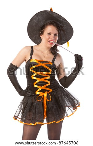 smiling girl in Halloween witch with wand - stock photo