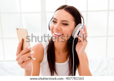 Smiling girl in headphones listening music on the background of window - stock photo