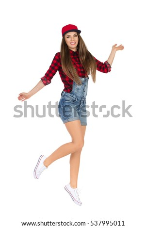 Smiling girl in red lumberjack shirt, jeans dungarees shorts, white sneakers and fullcap jumping and looking at camera. Full length studio shot isolated on white.