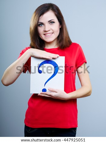 smiling girl in red shirt holding a question mark - stock photo