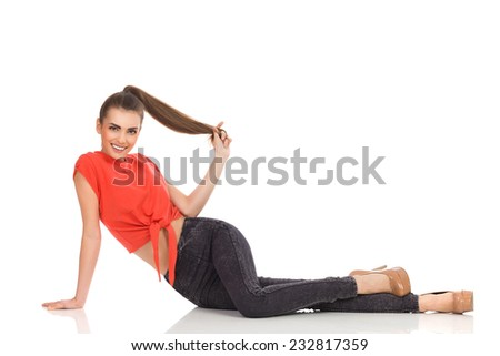 Smiling girl in red top, black jeans and high heels lying on the floor and holding a ponytail. Full length studio shot isolated on white. - stock photo