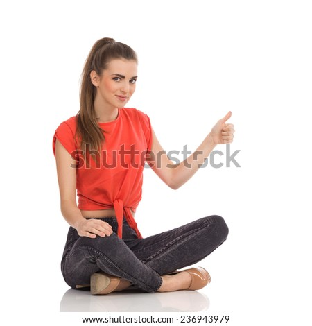 Smiling girl in red top, black jeans and high heels sitting with legs crossed on the floor and showing thumb up. Full length studio shot isolated on white. - stock photo
