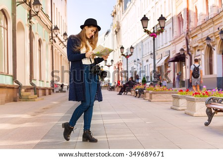 Smiling girl in retro outfit holding city map - stock photo