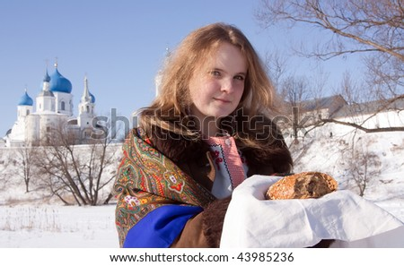 Smiling girl in russian traditional  clothes  with loaf against Orthodox monastery in  Bogolubovo.