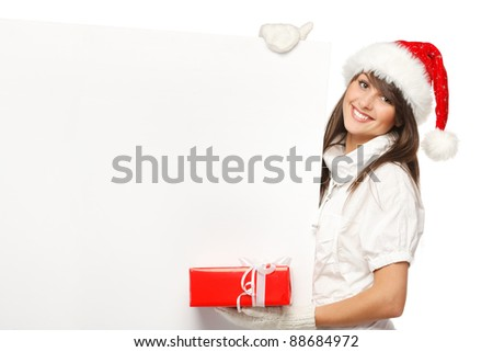 Smiling girl in Santa hat holding blank banner and a gift, isolated on white background - stock photo