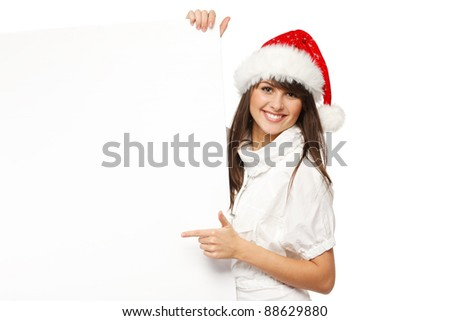 Smiling girl in Santa hat holding blank banner and pointing at it, isolated on white background