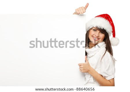 Smiling girl in Santa hat holding blank banner and showing thumb up sign, isolated on white background - stock photo
