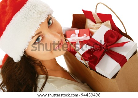 Smiling girl in santa hat with bag full of xmas gift isolated on white background - stock photo