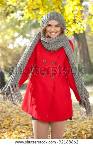 smiling girl in seasonal red coat, autumn park