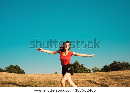 smiling girl in shorts and t-shirt run with open arms on the hill,  summer hot day, blue sky in background and dry grass - stock photo