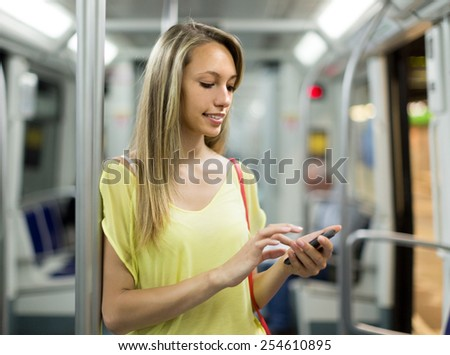 Smiling girl in subway train at metro using smartphone  - stock photo