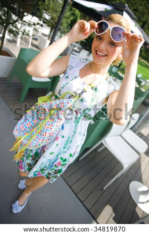 smiling girl in summer dress with bag on bar terace - stock photo