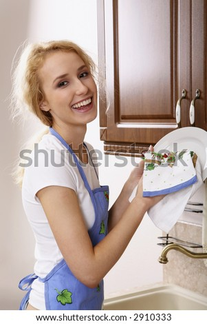 Smiling girl in the apron drying the dishes - stock photo