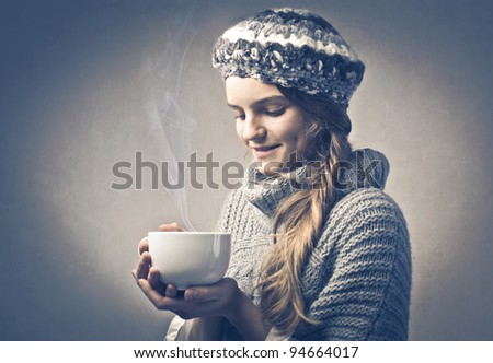 Smiling girl in warm clothes holding a bowl of hot drink - stock photo