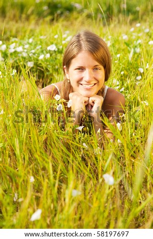 Smiling girl in white lying on meadow grass