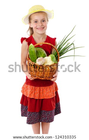 Smiling girl in yellow hat with basket of vegetables, isolated on white